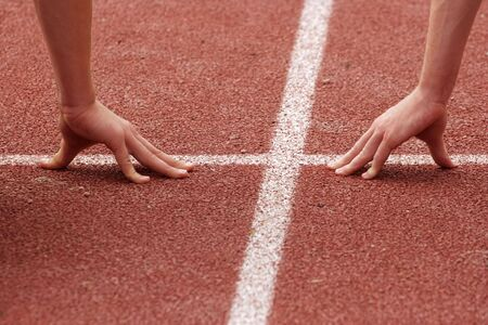poised: Hands poised at the starting line of a race