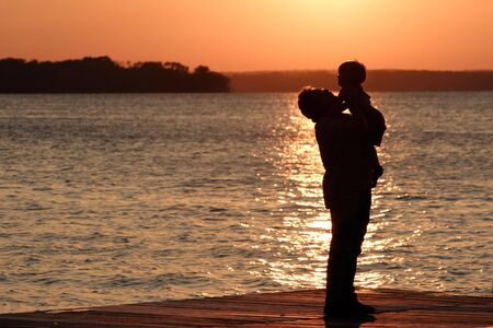 A father holds up his young sun while standing on the shore of a lake at sunset Stock Photo