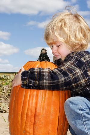 Young boy picks up the pumpkin that he has picked out from the pumpkin patch.