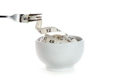 un tenedor recoge una cinta de medir de una taza de color blanco  Foto de archivo