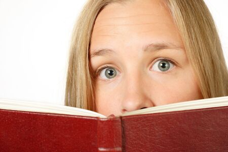 A teenaged girl looks over a book with a frightened look on her face photo