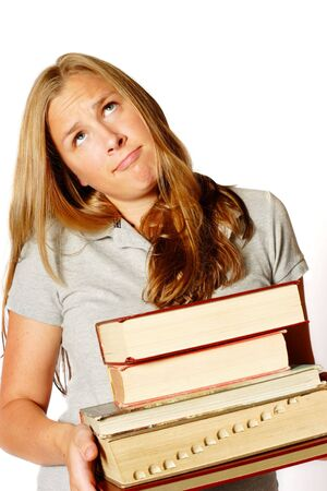 A teenage girl holding a pile of heavy books has a very frustrated look on her face photo