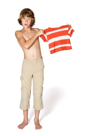 A teenager holds up a shirt that he has obviously outgrown. His pants are way too short photo