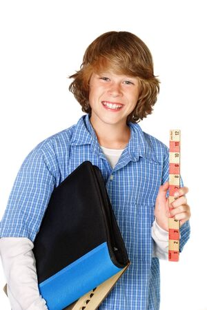 A teenager is ready for school. he is holding a ruler and he has his notebook and a dictionary under his arm