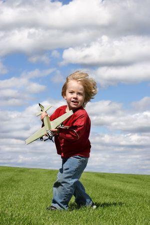 un muchacho joven con un aeroplano del juguete en hierba verde y un cielo azul con las nubes puffy
