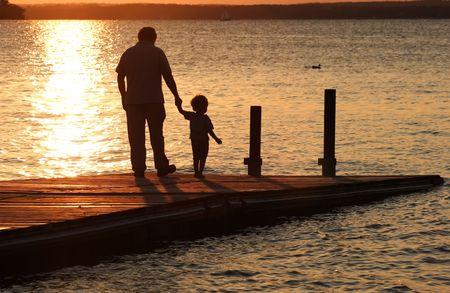 父は日没でドックに歩くと彼の息子の手を保持します。 写真素材