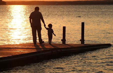 A father holds his sons hand as they walk out onto a dock at sunset. photo