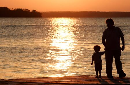 A father and son walk along the beach at sunset Reklamní fotografie