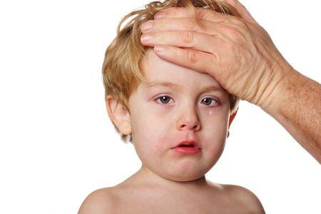 Un ni�o con los ojos llorosos se ve triste, mientras que un adulto los controles su frente para la fiebre