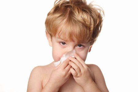 A sick young boy wiping his nose Stock Photo