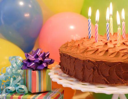 Een verjaardagstaart met kaarsen verlichte ballonnen en presenteert