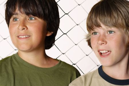 chums: Two boys standing in front of a baseball fence