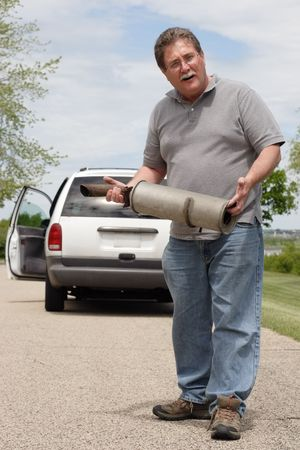 A man holds the muffler that just fell off of his car Stock Photo