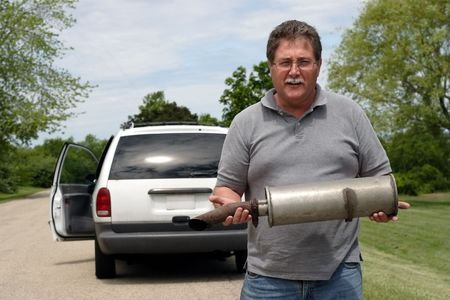 A man holds the muffler that just fell off of his car Banque d'images