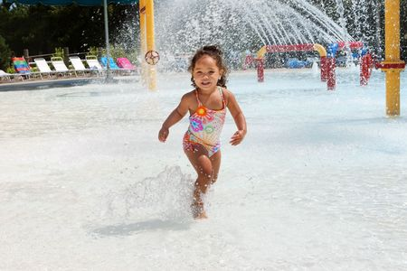 Young girl dances in the water at a waterpark. Water is spraying from a play system