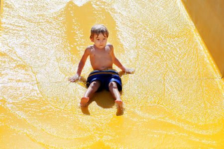 going down: a young boy going down a waterslide Stock Photo