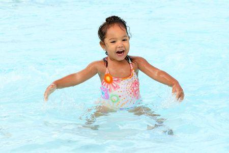 수영장에서 어린 소녀가 튀다.