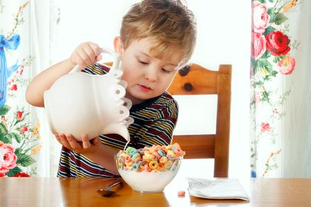 carbs: A young boy holding a pitcher pours milk into his cereal bowl.