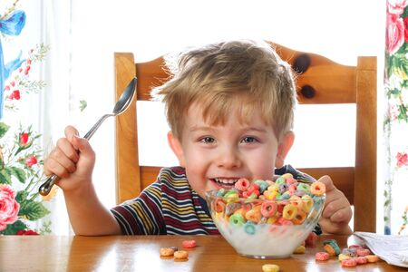 A young boy holding a spoon, smiles as he begins to eat a bowl of cereal