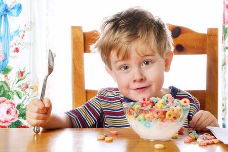 cereal: Chico joven se sienta a la mesa con un plato de cereal.