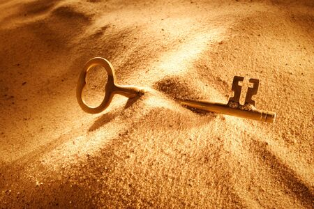 An old key laying in the sand photo