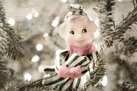 A vintage christmas ornament elf sits in a christmas tree photo
