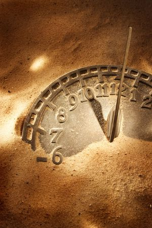 An antique sundial laying in the sand