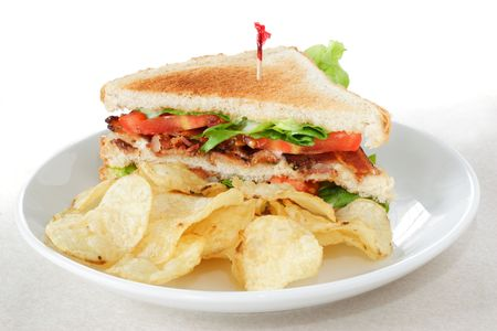 toothpick: Bacon lettuce and tomato sandwich on toasted bread served with potato chips
