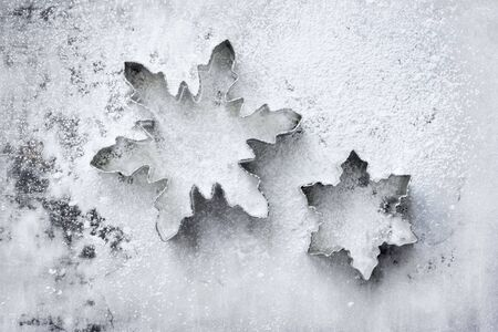 Snowflake cookie cutters on a powdered baking sheet photo
