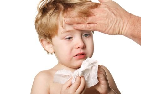A sick child blows his nose while his father touches his forehead Stock Photo