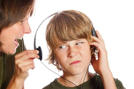 A mother pulls the headphone off of her son to tell him something