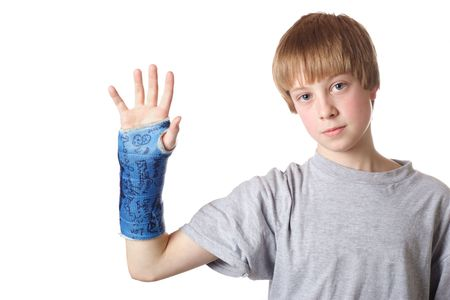 broken wrist: Teenage boy holds up his arm showing his cast