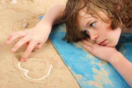 lays: Lovelorn teenage boy lays on the beach drawing a heart in the sand