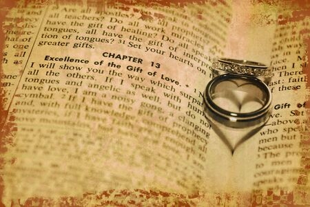 The shadows of of two wedding rings form hearts on the pages of a bible photo