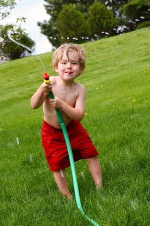 A young boy waving a hose and spraying water photo