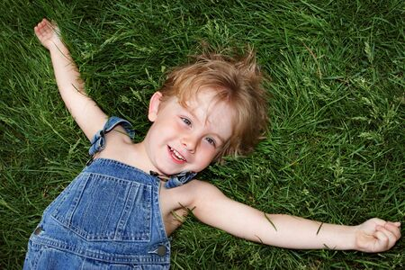 A boy in overalls laying on the grass photo