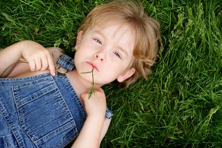 A boy in overalls laying down chewing on a blade of grass photo