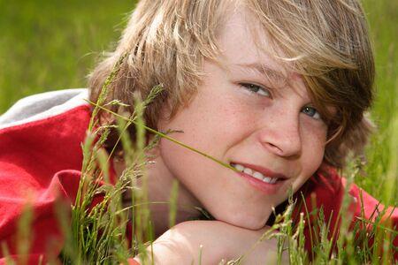 chłopięctwo: A teenage boy ustanawiające żucia na ostrzu trawy Zdjęcie Seryjne