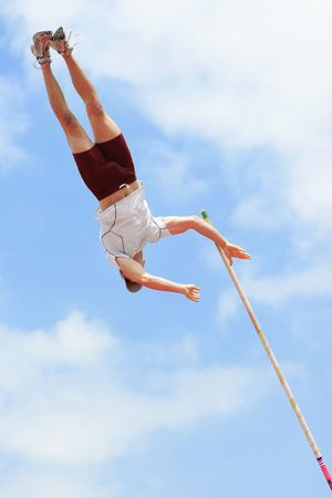 Pole vaulter has just released the pole while at the apex of his jump. Imagens