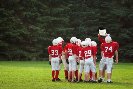 The coach holds up the play for the young football team.