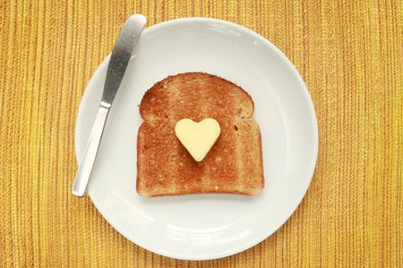 wheat toast: A piece of toast on a plate with a heart shaped pat of butter