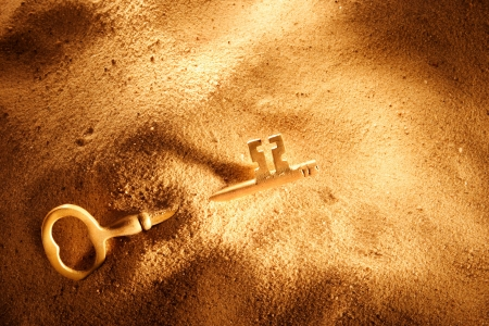 A skeleton key in a mound of sand photo