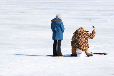 A man ice fishes as his wife looks on photo
