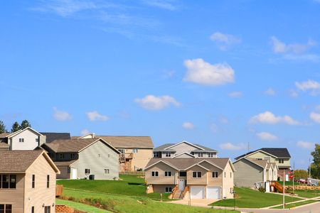 A modern neighborhood on a hill with a bright blue sky