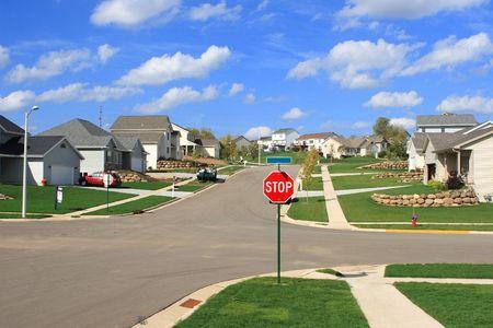 residential neighborhood: Una se�al de stop en la intersecci�n de un moderno barrio  Foto de archivo