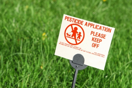 Pesticide warning sign on a bright green lawn Stock Photo