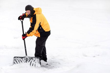 Winter scene with a man shoveling snow Standard-Bild