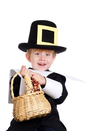 Young boy dressed as a pilgrim carrying a basket of corn Stock Photo
