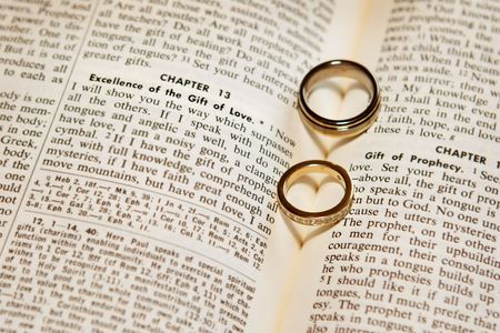The shadows of of two wedding rings form hearts on the pages of a bible