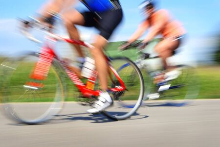 Two bicyclists in a race through the countryside  Stock Photo